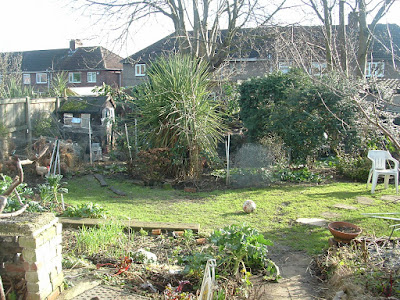 Photo of a back garden, showing an untidy patio, lawn, trees at the back, and chicken coop in the far corner
