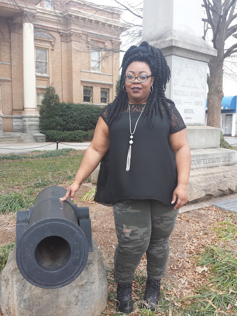 Plus size blogger wearing army fatigue, combat booties, black sheer blouse