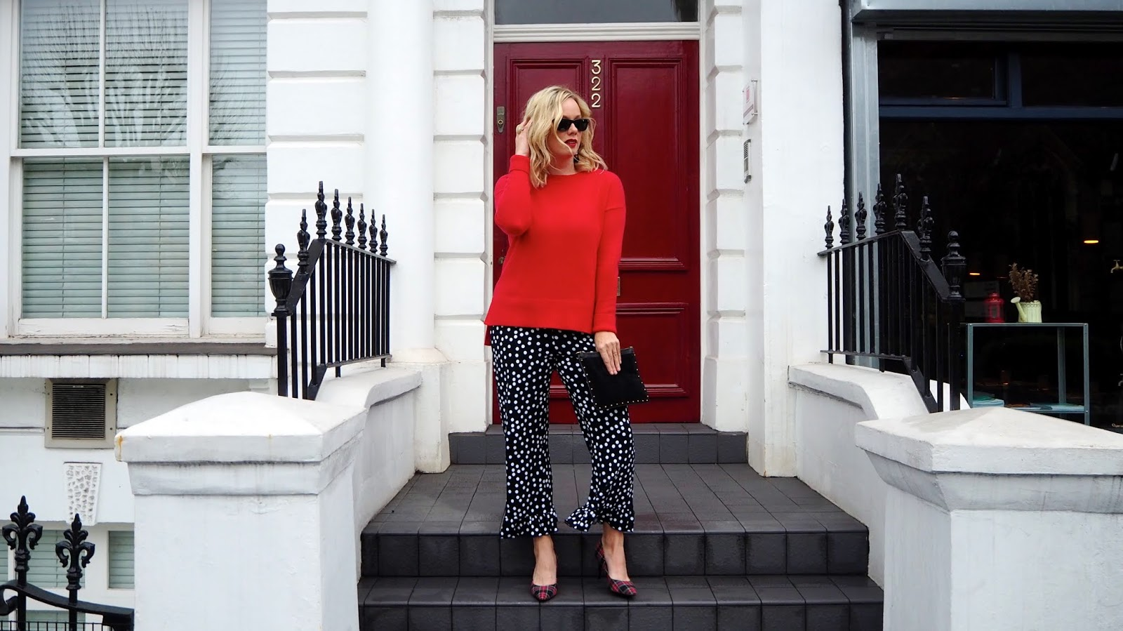 Ruffle hemmed black and white polka dot trousers, red plaid high heels, red sweater and black rayban wayfarer sunglasses