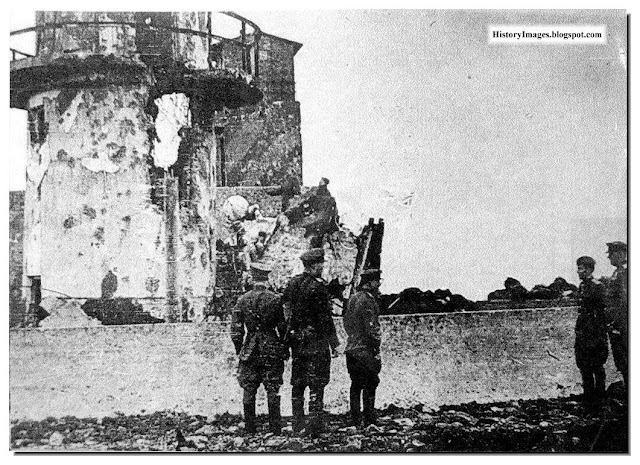 Red Army soldiers watch a Japanese lighthouse which they burnt at Cape Kokutan, Shumshu Islands, in Kuril Islands