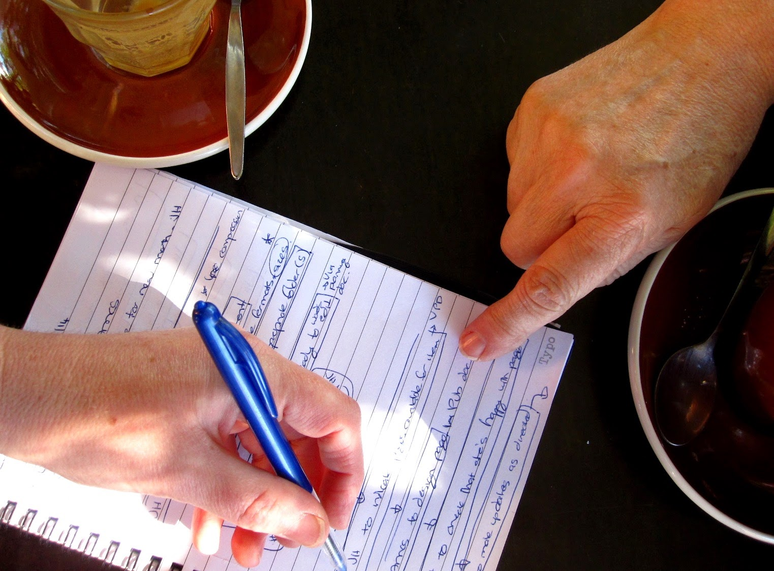 Aerial view of a cafe table, showing two empty coffee cups, a notebook page of notes, with one person pointing to it and the other making notations.