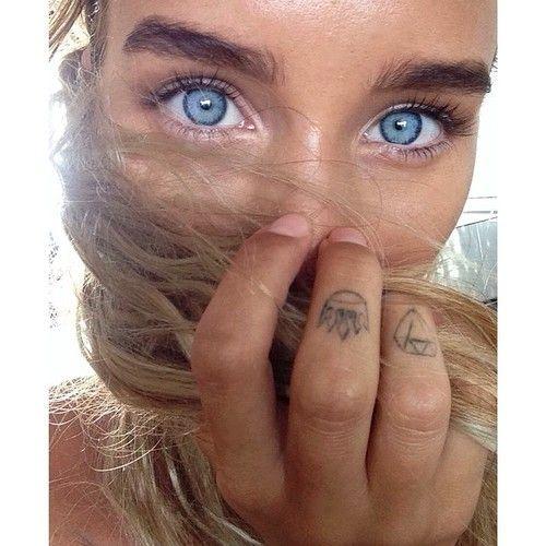 Imagen espectacular en primer plano de la mirada azul celeste de una chica, vemos en sus dedos tatuajes pequeños