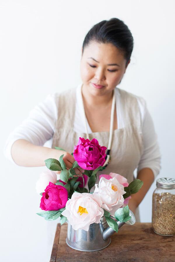Ji Kim arranging crepe paper peonies in metal watering can