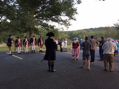 People in 18th century military uniforms and modern dress standing in parking lot
