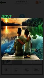 На закате на причале сидит друг и обнял свою девочку, смотрят на воду и солнце заходящее