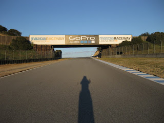 My shadow on the track approaching the overhead bridge before Turn 6, Mazda Raceway Laguna Seca, Salinas, California