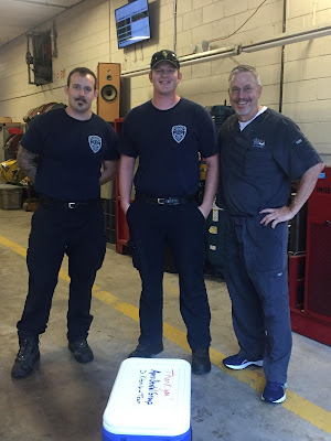 Dr. Kitzmiller stands with 2 fireman at Firestation 1.