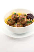 white bowl with swedish meatballs, egg noodles, lingonberry jam