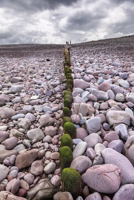 Multi coloured rocks at Bossington Beach in Exmoor National Park by Martyn Ferry Photography