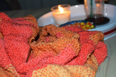 knitting an orange and yellow blanket and eating Candy Corn.