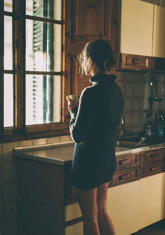 Garota tomando café na cozinha