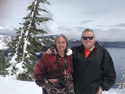 Us posing at Crater Lake. You can see Wizard Island in the background.