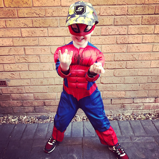 Little boy dressed like Spider-Man, whilst also wearing a baseball cap