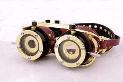 steampunk goggles that are wearable works of art. lenses have brass aperture shutters from cameras. Leather strap.