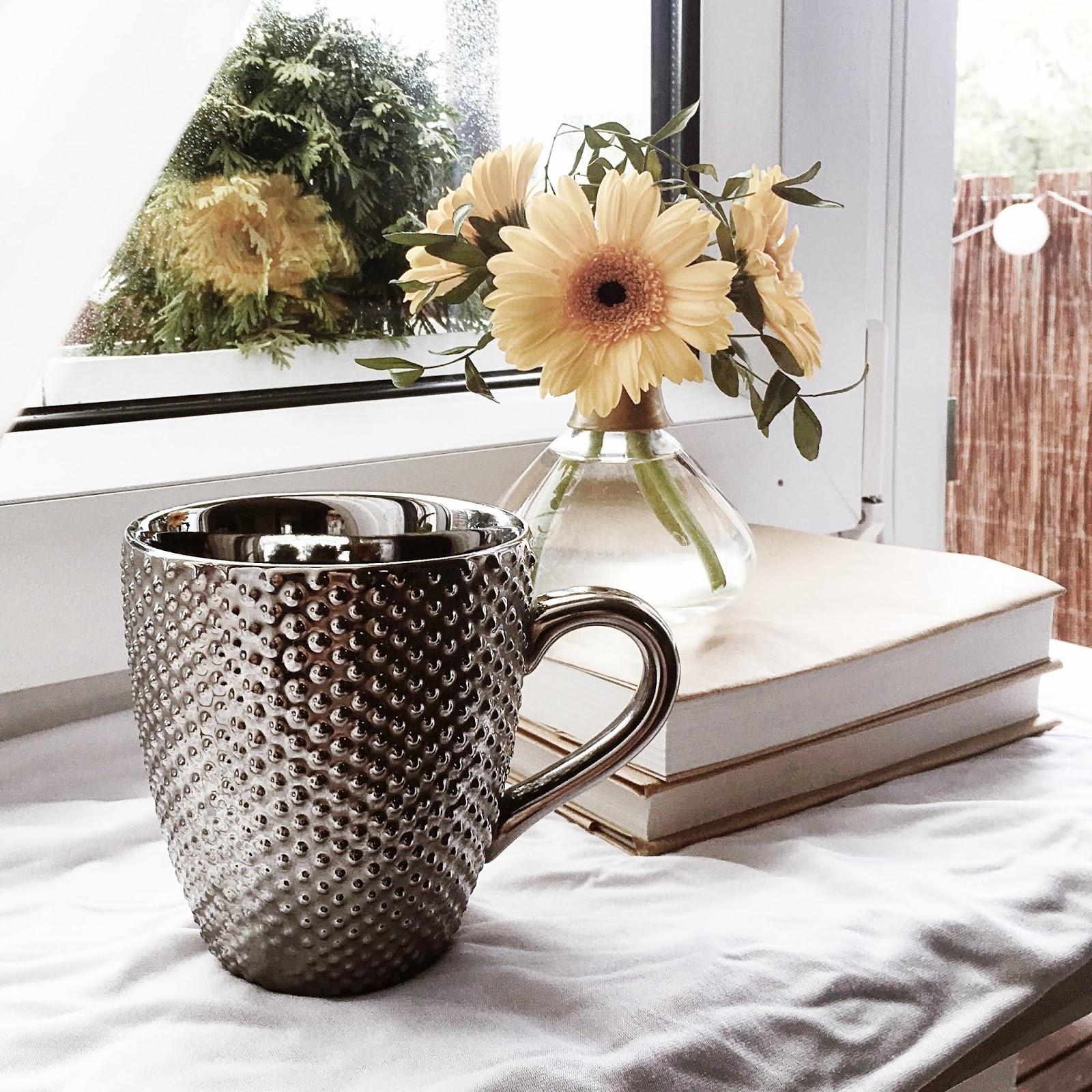srebrny kubek na parapecie na tle żółtych kwiatów