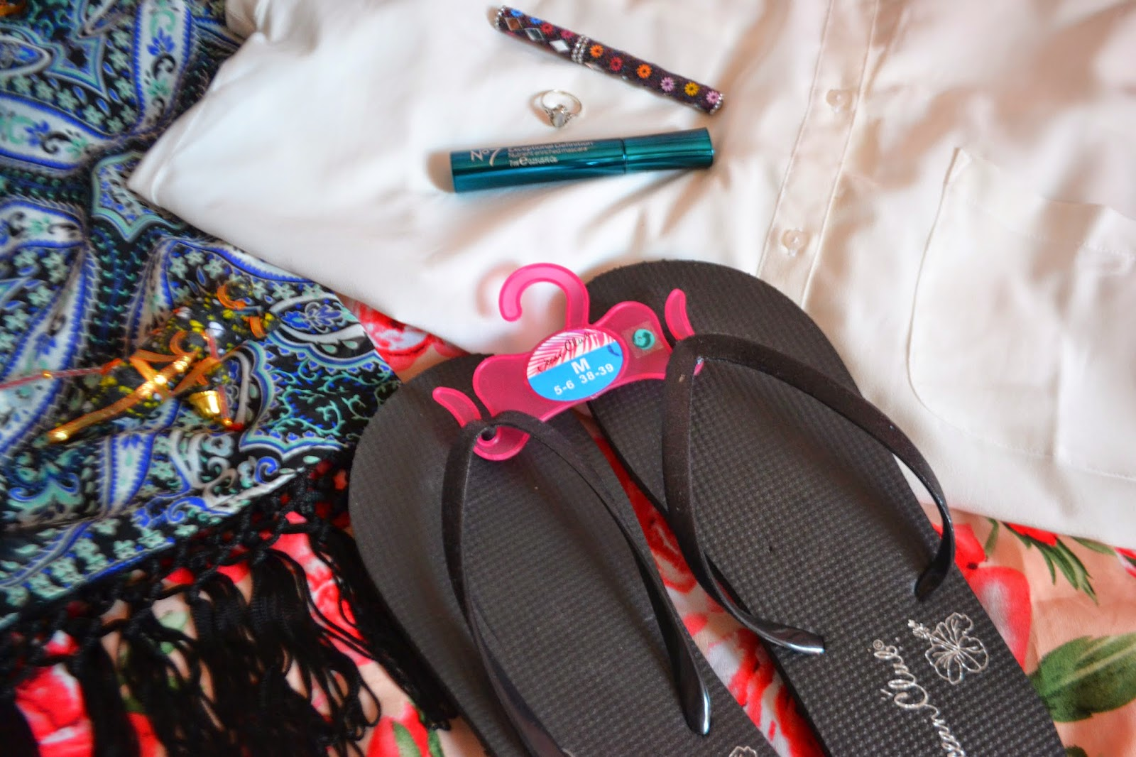 A shot showing the flip flops, the mascara, the string of elephants, the ring, and kimono, and the white blouse