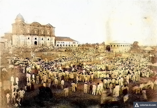 Crowds assembled in front of the Taal Basilica during the American colonial era.  Image source:  Luther Parker Collection.  Colorized courtesy of Algorithmia.