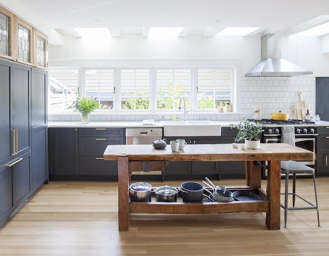 Bright, open kitchen features dark grey cabinetry, skylights and a rustic wooden table serving as a workspace in this 1927 craftsman heritage home in West Vancouver.