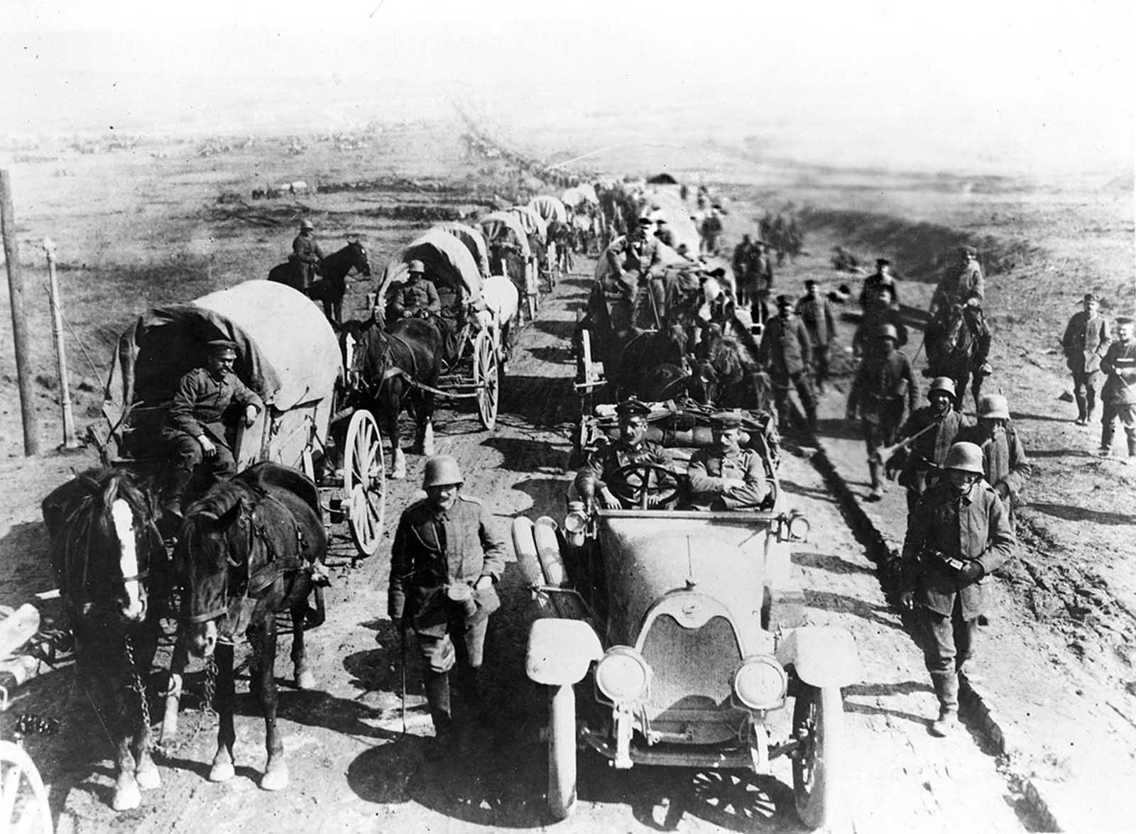 German officers in an automobile on the road with a convoy of wagons; soldiers walk along side the road.