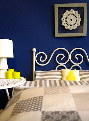 One-twelfth scale modern miniature bedroom with deep blue wall, white wire bed and side table and grey and white bedding.