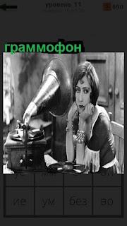 За столом сидит женщина и слушает старинный граммофон