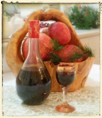 kieliszek likieru, butelka z likierem, kosz z owocami granatu, czerwone granaty
