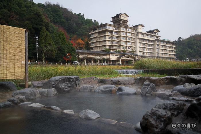 vue sur l'un des bassins publics, et un ryokan en fond