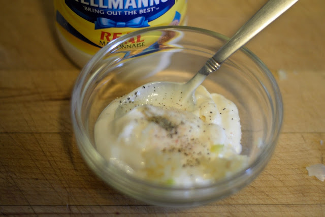 Salt and pepper being added to the mayonnaise.
