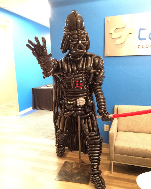 A life size balloon sculpture of Darth Vader Posing with a lightsaber and his hand up