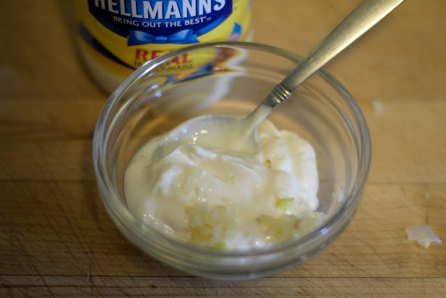 Garlic being added to the mayonnaise.