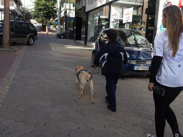 παιδάκι κάνει βόλτα με σκύλο οδηγό