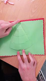 As mãos de um aluno a elaborar um postal com uma árvore de Natal em pop-up