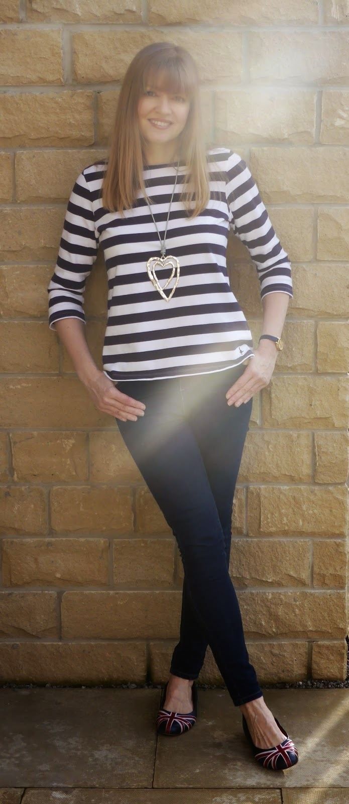 Navy and white striped breton top, skinny jeans, large metal heart pendant