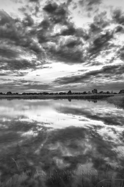 Dramatic cloud reflections at Cambridgeshire RSPB nature reserve by Martyn Ferry Photography