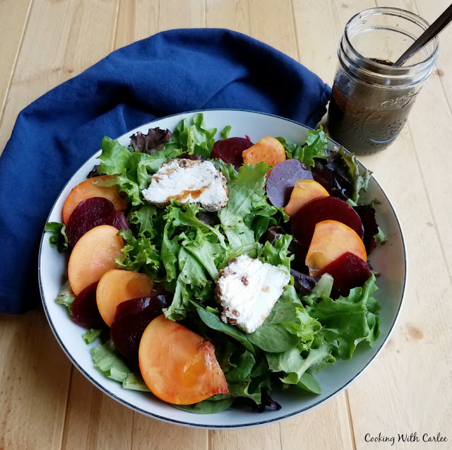 greens topped with sliced beets, persimmons and goat cheese with jar of dressing