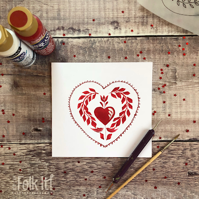 White card painted with a traditional folk art design in red created by Carol Sykes from you Can Folk It.