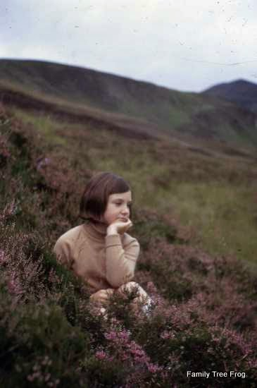 Alex sitting in heather in Scotland, thinking