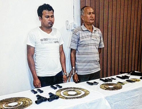 Umesh Kami and Ganesh Chhetri with the arms and ammunition in Assam.