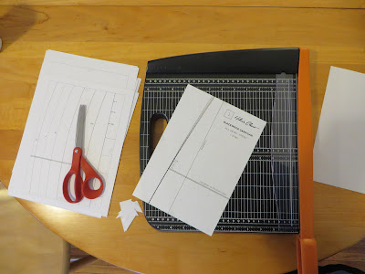 Scissors, printed PDF pattern with a trimmed page, and paper trimmer.