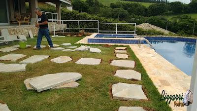 Bizzarri organizando para executar os caminhos de pedra no jardim em volta da piscina sendo a execução do caminho de pedra Carranca tipo cacão com junta de grama em casa em condomínio na represa de Piracaia-SP.