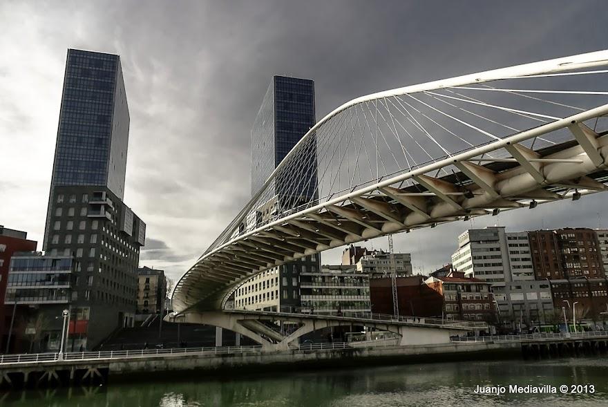 Puente Zubizuri o puente de Calatrava. Al fondo las torres de Isozaki