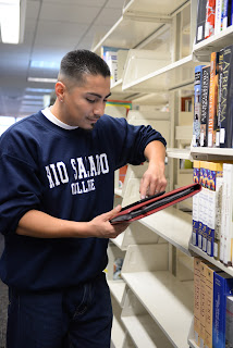 image of student in Rio Salado College sweatshirt in the library looking at books