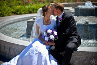 Professional quality traditional wedding portrait photograph of a bride and groom sitting on fountain kissing in Brigham City, Utah by Cramer Imaging