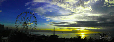 Panoramic view of the giant ferries wheel and Manila Bay sunset at SM Mall of Asia bay area