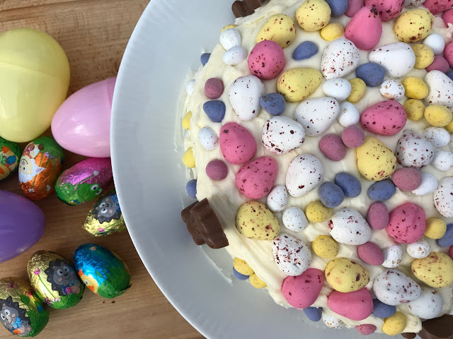A cake covered in frosting, chocolate eggs and bunnies
