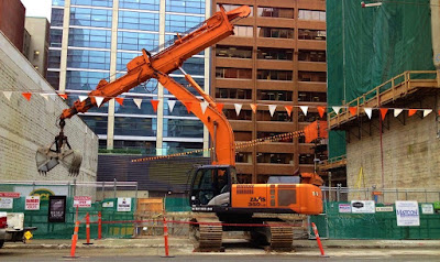 Clamshell digger on street in front of construction site.