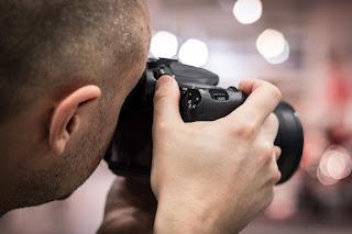 Ein Mann mit Kamera, der Fotos von einer Person macht.