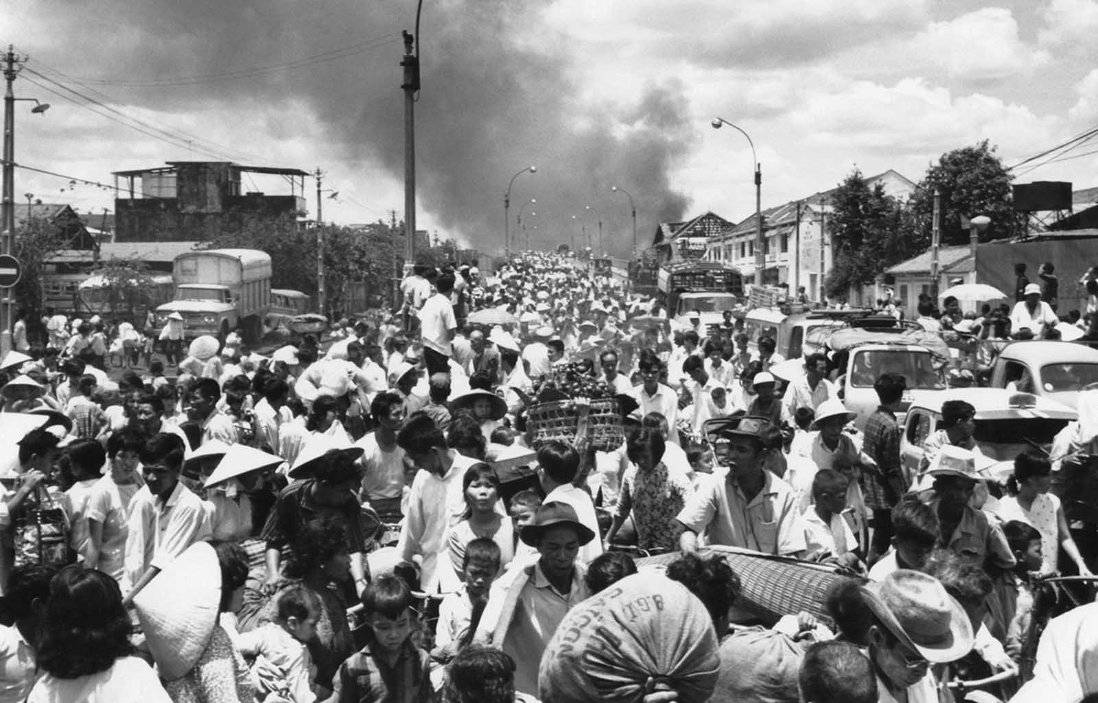 Smoke rises from the southwestern part of Saigon on May 7, 1968, as residents stream across the bridge leaving into the capital to escape heavy fighting between the Viet Cong and South Vietnamese soldiers.