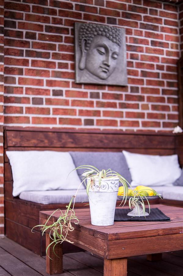 Blog + Fotografie by it's me | fim.works | Ein Garten im Norden | Lounge-Ecke vor roter Steinwand | Buddha-Bild