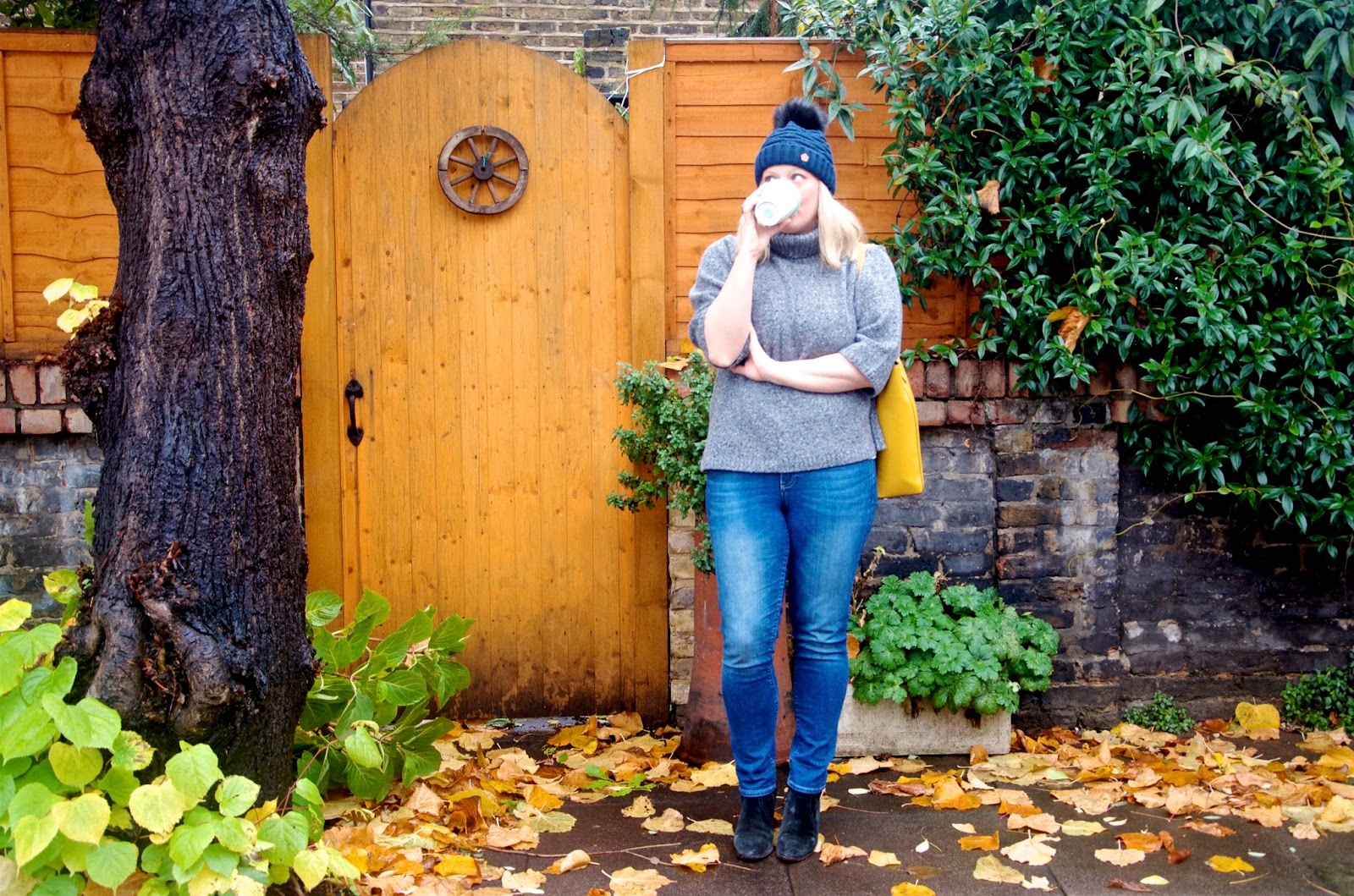 Coffee, wagon wheel gate, grey sweater, denim, fur beanie and yellow bag